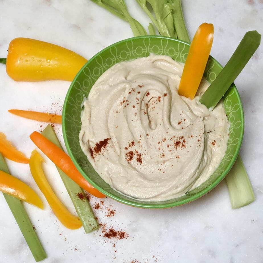 Heavenly homemade hummus in bowl with celery and pepper strips