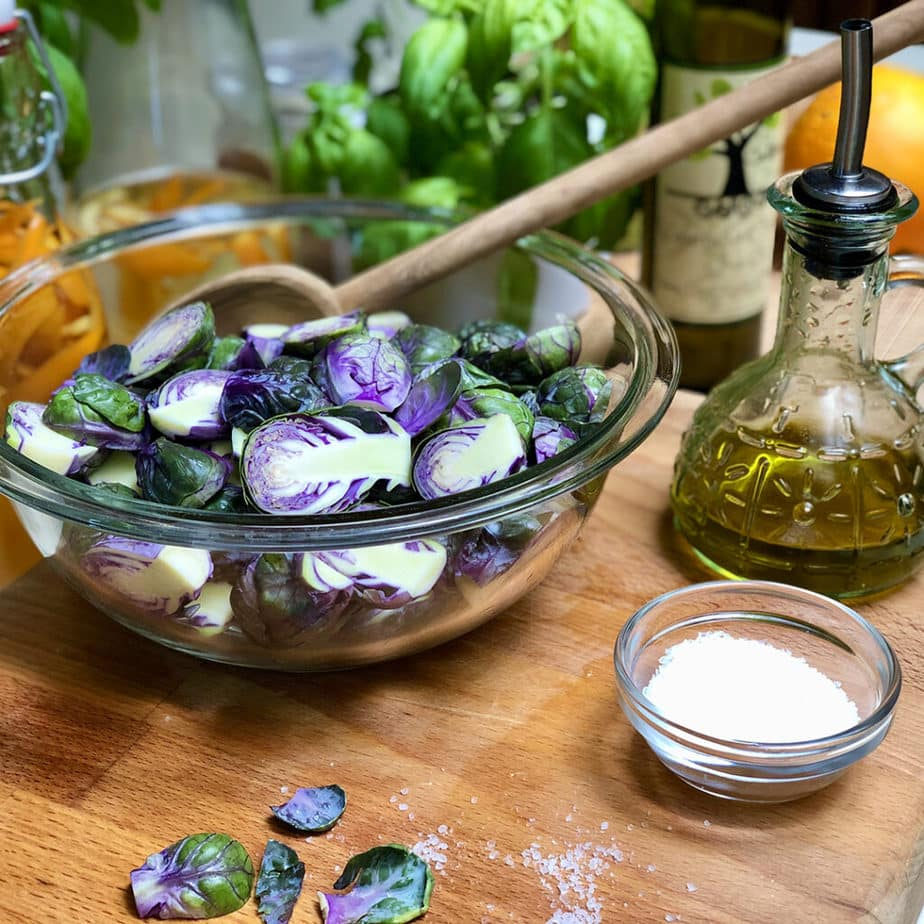 purple brussels sprouts in a clear bowl with salt & olive oil