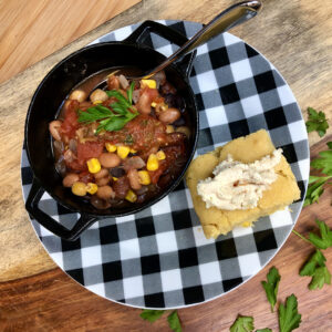 bowl of vegan chili and cornbread on plate