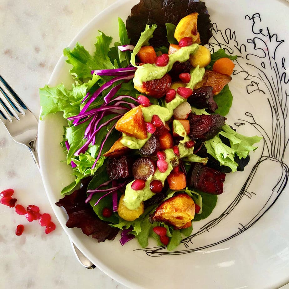 Roasted carrots and beets served on a plate with romaine, red cabbage, vegan avocado basil dressing and pomegranate seeds.