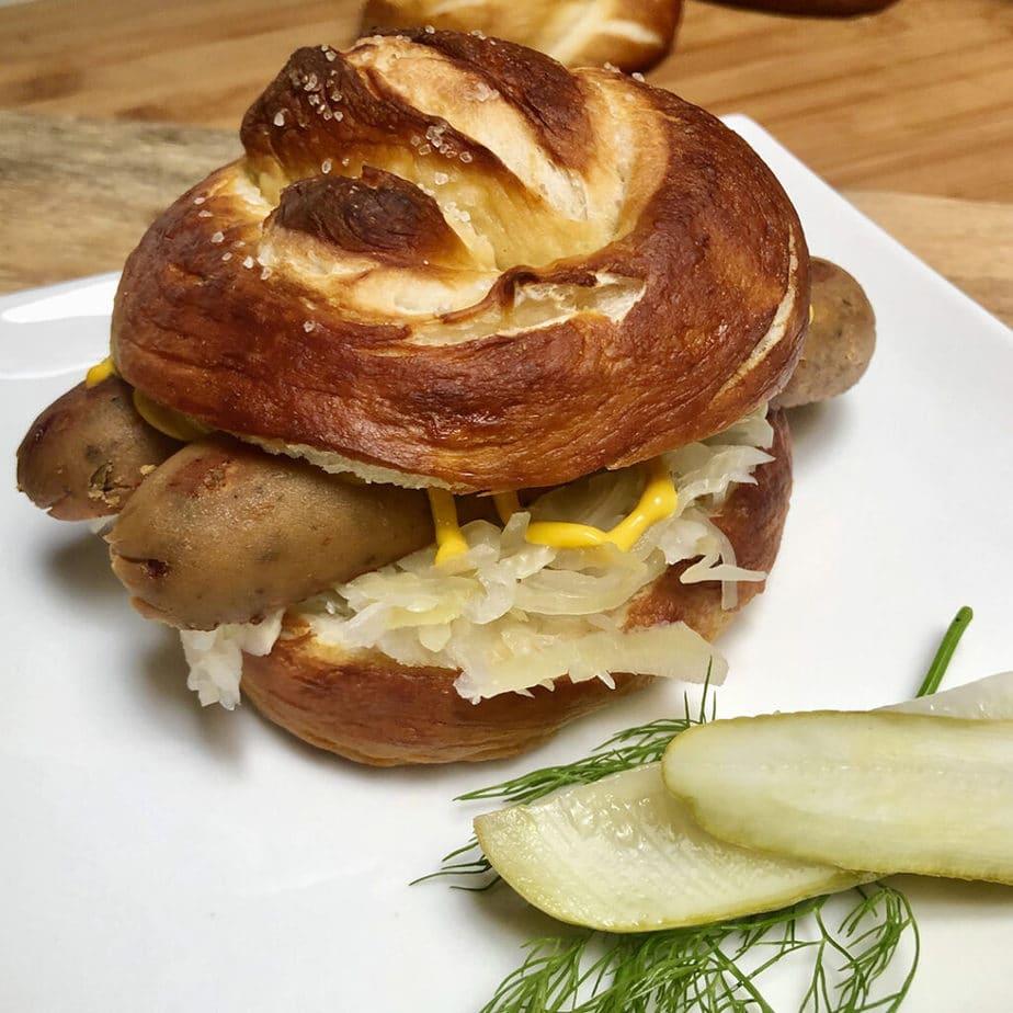 vegan sausage and saurkraut sandwich on pretzel bun