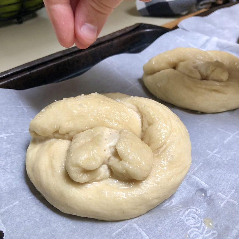 sprinkling unbaked pretzel with salt